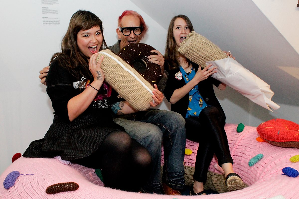 "Alyssa Arney, Glenn Zucman & Liz Flynn, sitting in a giant, crocheted, pink donut at the opening of Alyssa & Liz' exhibition ""Pleasure Objects"" at Gallery 211 in Santa Ana, California"